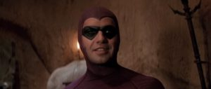Image is a screen cap from the movie featuring Zane suited up as The Phantom, regarding someone offscreen with a bemused expression.
