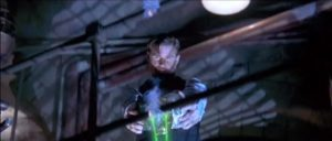 Image is a screen cap from the movie featuring Treat Williams as Xander Drax, holding the four skulls and shooting laser beams downward as he looks on.
