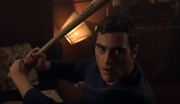 Image is a screen cap from the movie Signs. Joaquin Phoenix is gripping a baseball bat and looking determined at the alien attacker off camera.